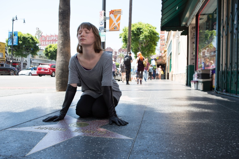 Agatha (Mia Wasikowska) communes with the ghost of a faded star on Hollywood's Walk of Fame in MAPS TO THE STARS (2014)